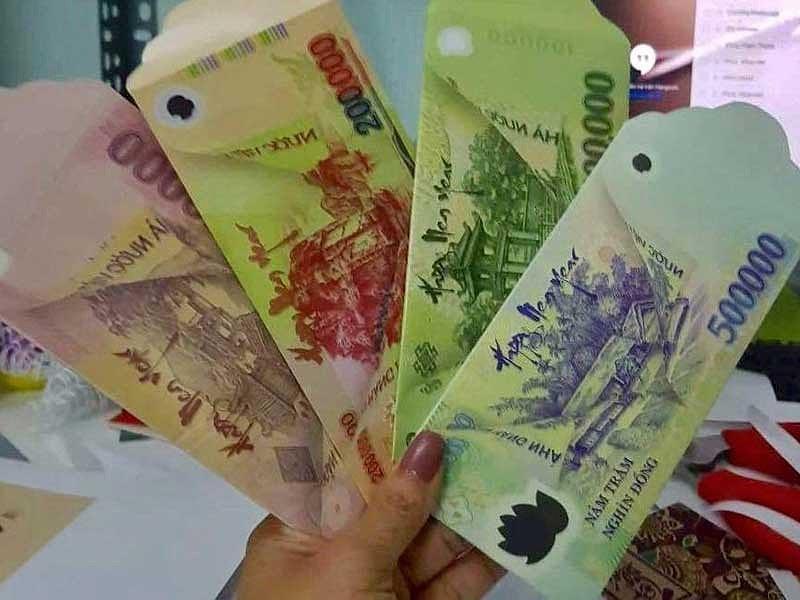 Các mẫu bao lì xì có in hình những tờ tiền đang lưu hành. Mặt bên kia của mẫu bao lì xì có hình ảnh giống hệt mặt còn lại của các tờ tiền này. Ảnh: TH